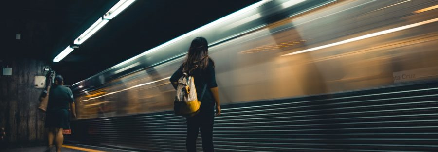 woman standing beside train station